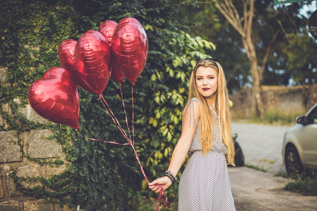 woman holding some heart shaped balloons