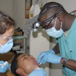 two dentist checking the patient's mouth
