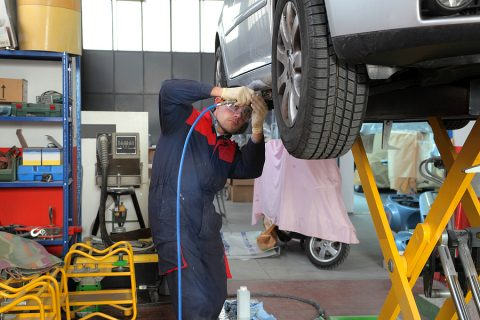 Mechanic using a workshop equipment to fix a tyre
