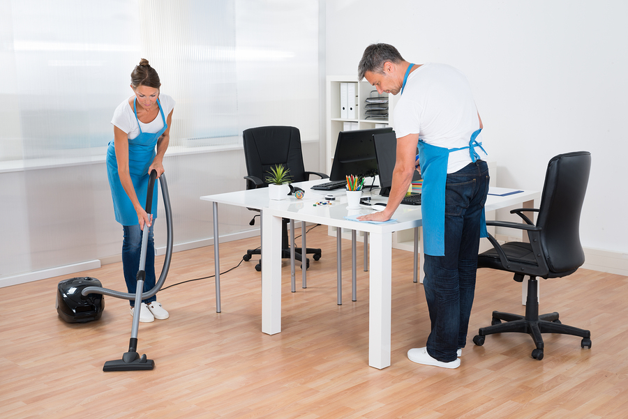 Two workers of a rubbish removal Sydney company cleaning an office